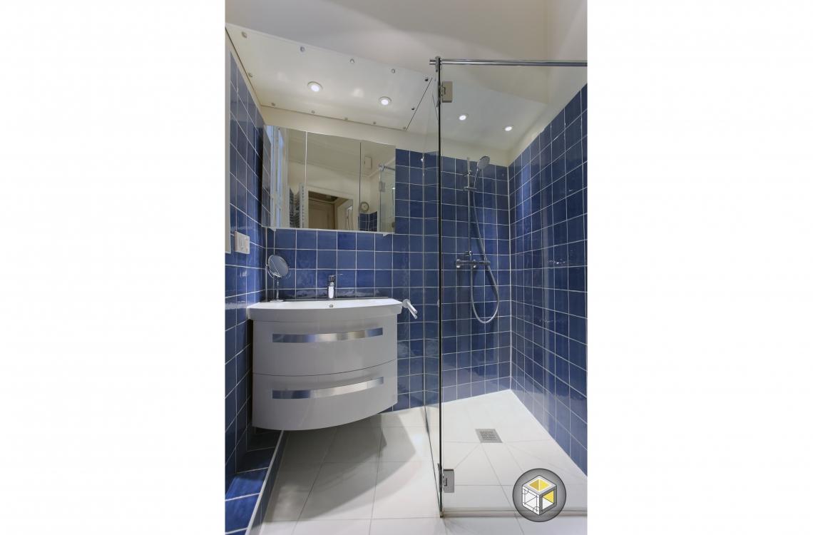 salle de bain carrelage bleu douche parois transparentes